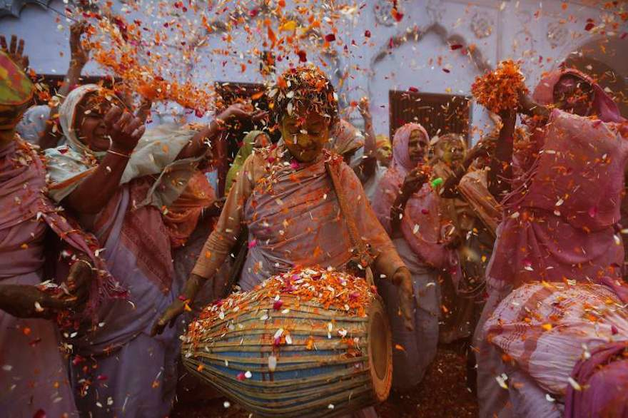 Widows dance as they throw flowers into the air during Holi celebrations organised by non-governmental organisation Sulabh International Vrindavan