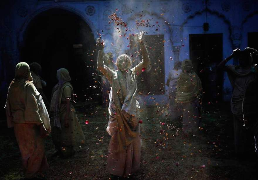 A widow throws flower petals as she, along with others, take part in the Holi celebrations organised by a non-governmental organisation Sulabh International at a widows' ashram at Vrindavan in the northern Indian state of Uttar Pradesh