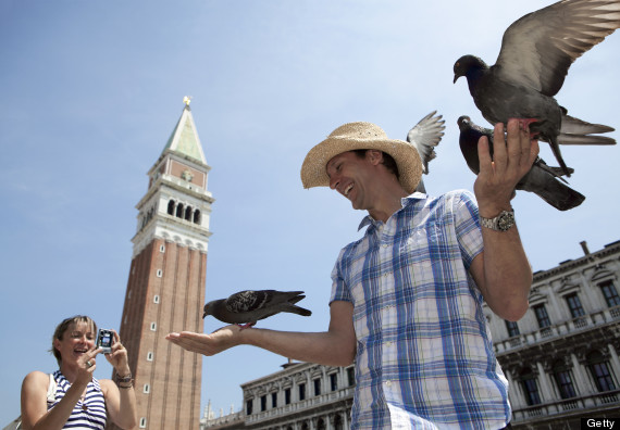 Man feeding pigeons in St Marks Square, Venice