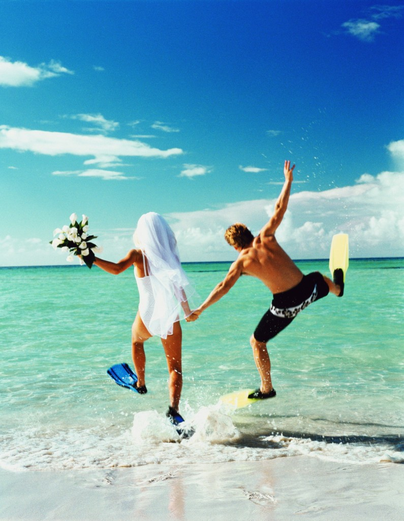 Bride and groom wearing flippers, running into sea (Enhancement)