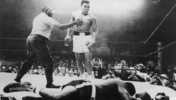 """(FILES) A picture taken 26 May, 1965, in Lewiston, Maineduring the world heavyweight boxing championship, at the end of which the American Muhammad Ali (Cassius Clay) (C) won against his compatriot Sonny Liston (R) after a one minute fight with Joe Walcott (L) as a referee. Ali celebrated his 65th birthday privately in Phoenix, Arizona 17 January, 2007 in his suburban home while his legacy was honored and marketed to a new generation of fans. Ali and his wife Lonnie moved to Arizona from Michigan four months ago, where warmer weather will help comfort """"The Greatest"""" as he deals with Parkinson's disease that has weakened his body but not his mind."""